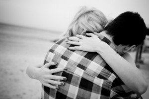 The back view of a couple embracing at the beach. No visible faces showing. Black and white image.